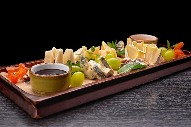 Plateau de fromages sur une planche en bois avec raisins, menthe, miel et confiture, sur une table noire, vue latérale
