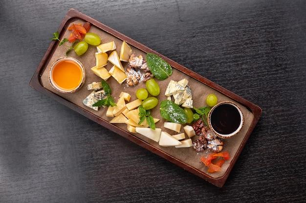 Plateau de fromages sur une planche en bois avec raisins, menthe, miel et confiture, sur une table sombre, vue du dessus