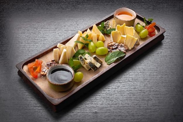 Plateau de fromages sur une planche en bois avec raisins, menthe, miel et confiture, sur une table sombre