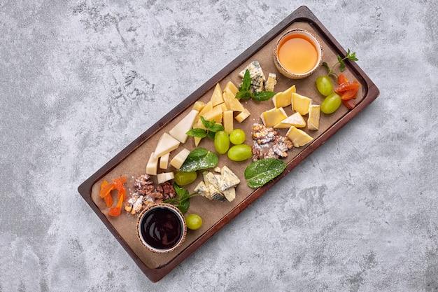 Plateau de fromages sur une planche de bois avec raisins, menthe, miel et confiture, vue du dessus