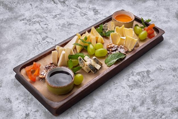 Plateau de fromages sur une planche en bois avec raisins, menthe, miel et confiture