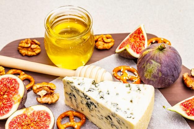 Plateau de fromages (planche) avec fromage bleu, miel, noix, figues, bretzels