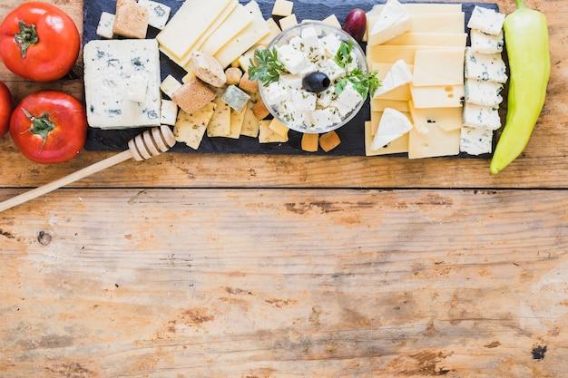 Plateau de fromages servi avec tomates rouges et poivrons verts sur une table en bois