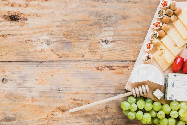 Plateau de fromages servi avec des tomates rouges et des raisins sur une table en bois
