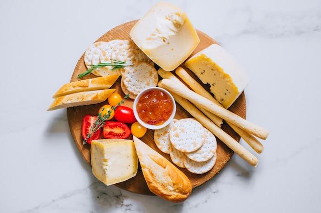Plateau de fromages avec tomates, confiture, baguette, bâtons de pain et craquelins