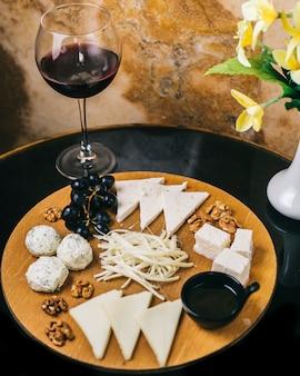 Plateau de fromages avec un verre de vin rouge.