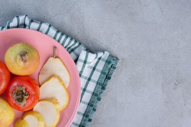 Un plateau de fruits aux poires et kakis sur une serviette, sur fond de marbre.