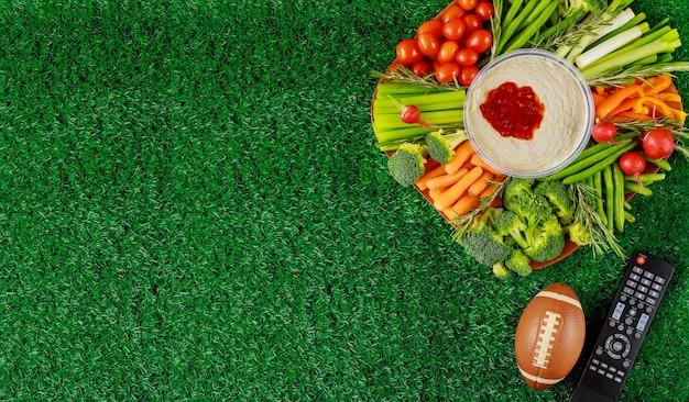 Plateau de légumes coloré avec ballon de football pour partie de match de football américain. vue de dessus, copiez l'espace.