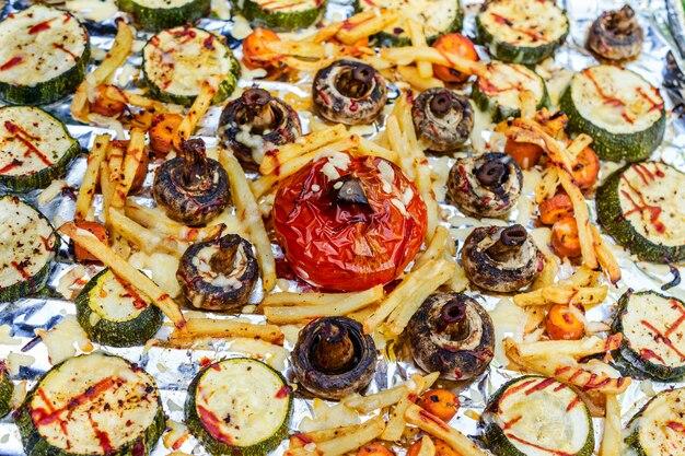 Plateau avec des légumes frits préparés sur le gril sur le papier d'aluminium. fermer.