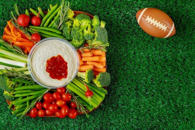Plateau de légumes sains avec ballon de football pour fan de football américain. fermer.