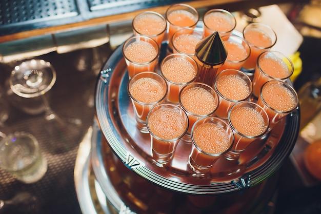 Un plateau en métal argenté rempli de tous les verres à liqueur de vodka, de gin et de tequila clarifie l'alcool pur.
