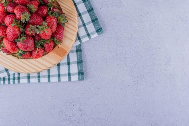 Plateau sur une nappe pliée avec un tas de fraises sur fond de marbre. photo de haute qualité