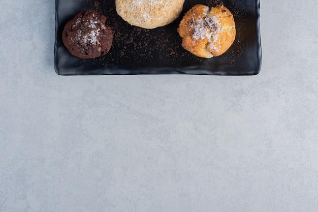 Plateau noir avec divers petits gâteaux sur une surface en marbre
