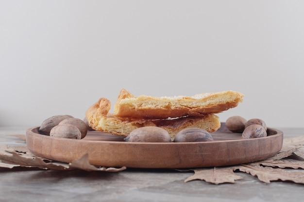 Un plateau avec des noix de pécan et des tranches de pain plat feseli sur marbre