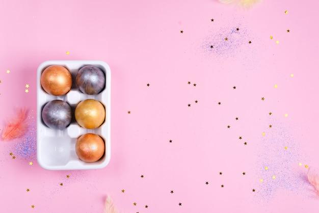 Plateau d'oeufs en céramique avec des oeufs de pâques peints en or et argent sur fond d'étoiles roses, concept de vacances