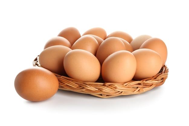 Plateau en osier avec des œufs de poule brun cru sur fond blanc