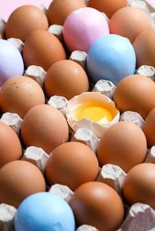 Plateau en papier artisanal avec des œufs biologiques naturels et peint à la main avec un jaune dans une coquille