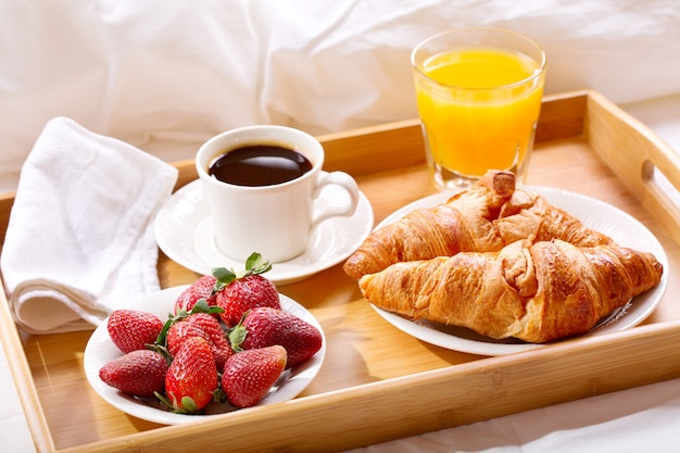 Plateau petit déjeuner au lit: café, croissants, jus de fruits et fraises fraîches