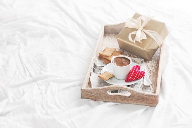 Plateau de petit déjeuner avec café, un cadeau et un coeur
