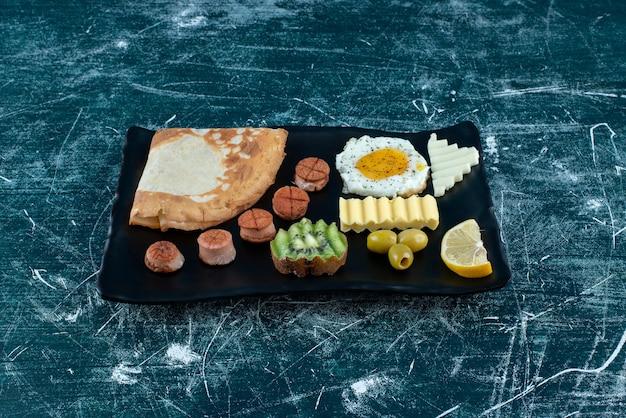 Plateau de petit-déjeuner avec crêpes, œuf au plat et ingrédients d'accompagnement.