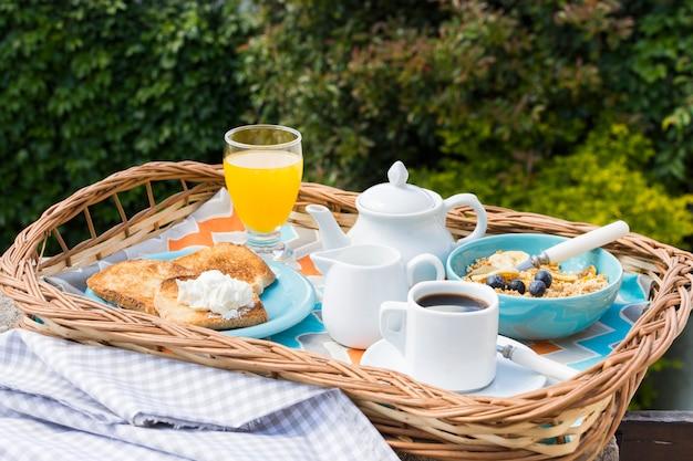 Plateau de petit déjeuner délicieux dans le jardin