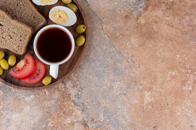 Plateau de petit déjeuner avec du pain et une tasse de thé