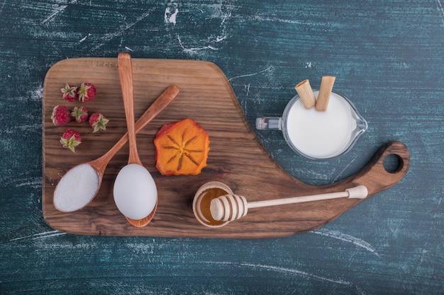 Plateau de petit-déjeuner avec des ingrédients sur une planche de bois, vue du dessus
