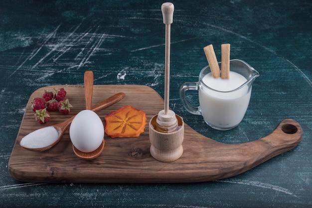 Plateau de petit-déjeuner avec des ingrédients sur une planche de bois