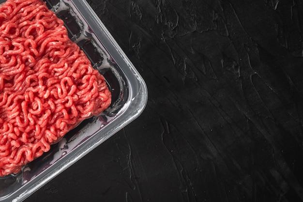 Plateau en plastique ouvert avec de la viande de bœuf hachée crue fraîche, sur une table en pierre noire, vue de dessus à plat