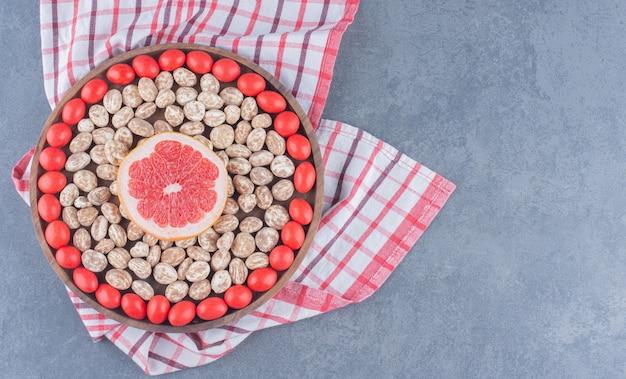 Plateau plein de biscuits et de gommes avec pamplemousse au milieu, sur le fond de marbre.