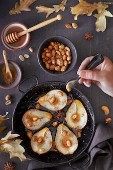 Plateau de poires au four avec noix caramélisées avec feuilles sèches, sucre, cannelle et miel