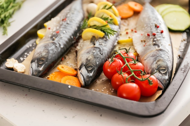 Plateau avec poisson maquereau cru et légumes sur table