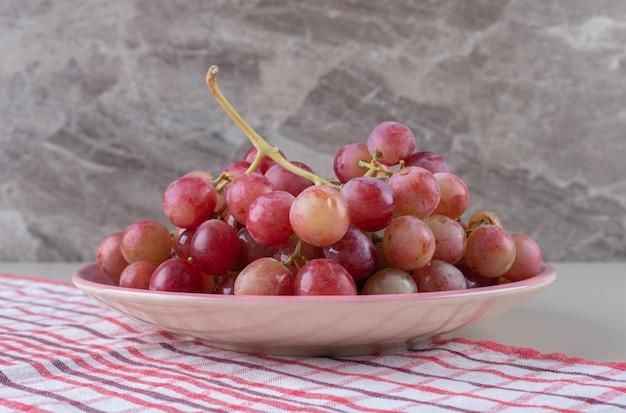 Plateau de raisins sur une serviette sur marbre