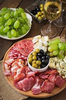 Plateau de restauration antipasto avec bacon, saccadé, salami, fromage et raisins sur une table en bois