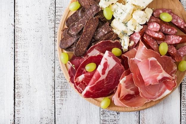 Plateau de restauration antipasto avec bacon, saccadé, saucisse, fromage bleu et raisins