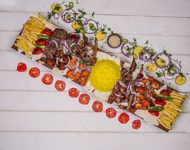 Plateau de restauration avec kebab traditionnel, grillades et légumes.