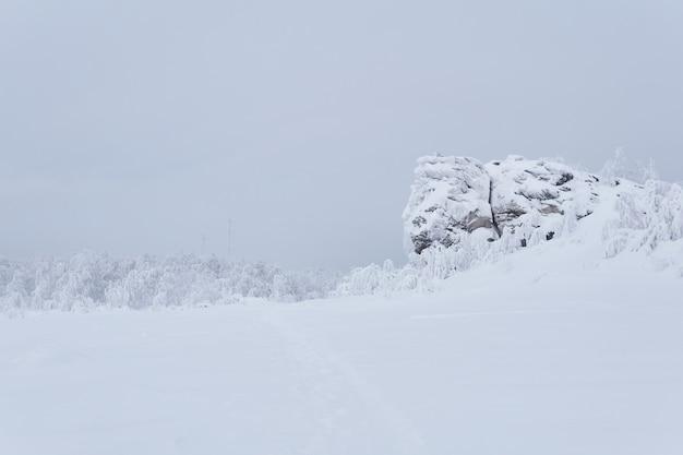 Plateau rocheux recouvert de neige profonde des tours cellulaires sont visibles au loin dans le brouillard