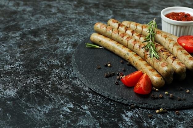 Plateau avec saucisse grillée, épices et sauce sur fond noir fumé