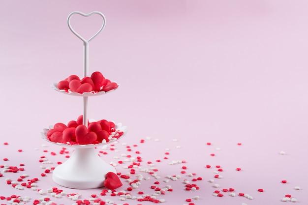 Plateau de service blanc à deux niveaux plein de cœurs de bonbons sucrés multicolores. amour et concept de la saint-valentin.