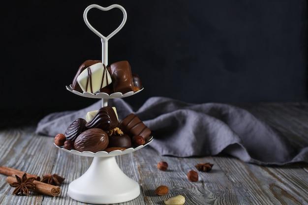 Plateau de service blanc à deux niveaux plein de confiseries sucrées avec des bonbons au chocolat et des pralines aux noix