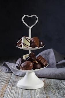 Plateau de service blanc à deux niveaux plein de confiseries sucrées avec des bonbons au chocolat et des pralines