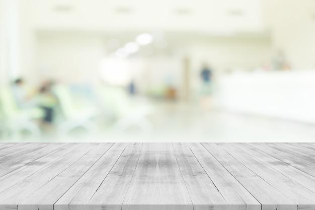 Plateau de table en bois blanc vide sur l'intérieur de l'hôpital flou pour le fond, espace pour les produits de montage