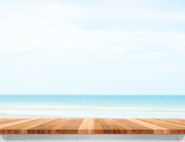 Plateau de table en bois avec mer floue et ciel bleu au fond