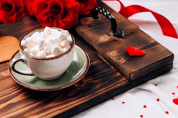 Plateau avec tasse à café sur lit et fleurs, petit-déjeuner romantique