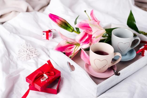 Plateau avec une tasse de thé chaud dans le lit