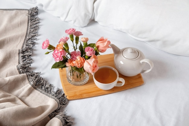 Plateau de thé sur le lit. draps blancs avec couverture et oreiller. petit déjeuner au lit. concept hygge scandinave chaleureux et confortable - tasse de thé.