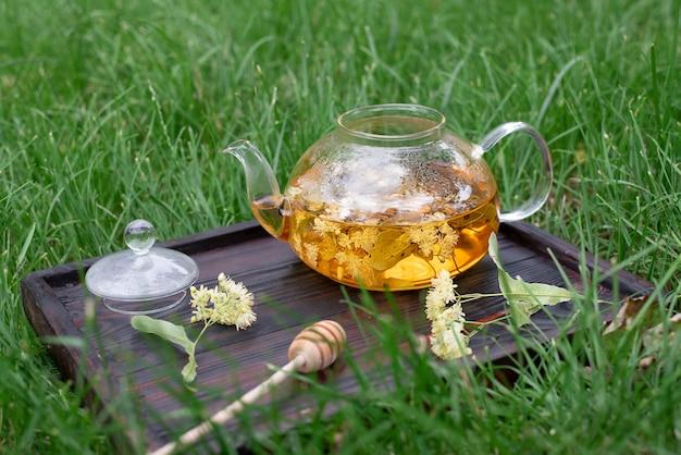 Un plateau avec une théière en verre avec du thé de tilleul sur l'herbe, une tisane saine, en gros plan.