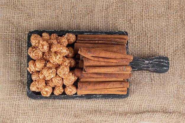 Plateau usé avec des piles de bonbons de maïs soufflé et des coupes de cannelle sur table textile.
