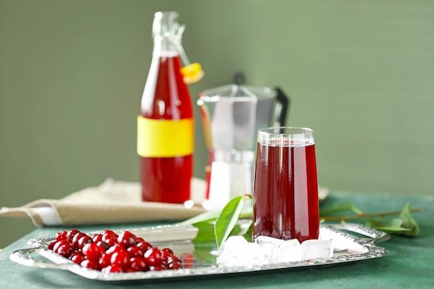 Plateau avec verre de délicieux jus de cerise et glace sur table