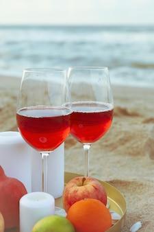 Plateau avec verres de vin, fruits et bougies sur la plage de sable de la mer
